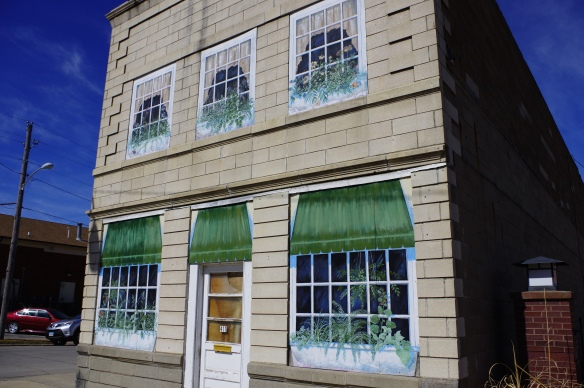 Boarded up windows painted in trompe l'oeil style.